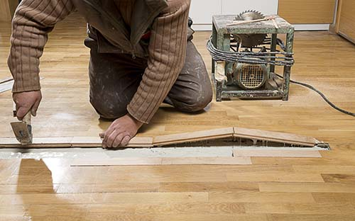 Image of man repairing hardwood flooring