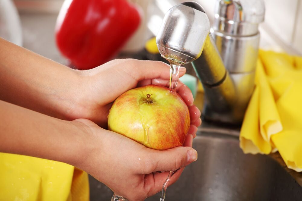 Image showing a person washing an apple at the sink