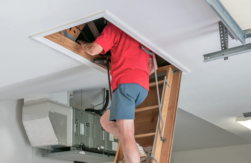 Image of man inspecting the attic area in a house