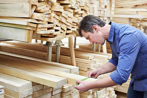 Image of a man inspecting lumber