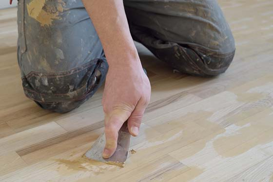 Image of a man repairing a hardwood floor