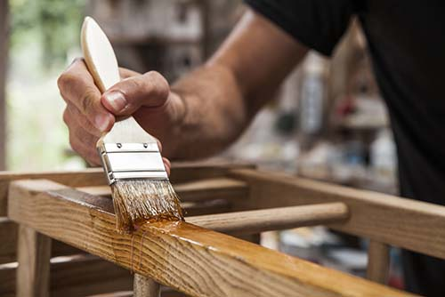 Image of a man sealing wood with a paint brush