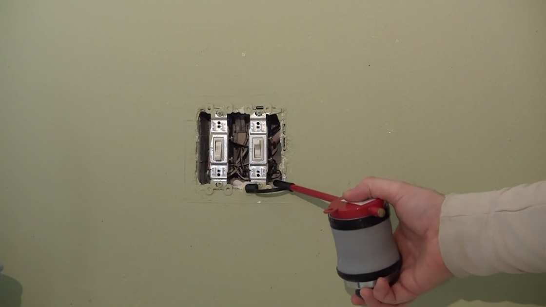 An image of a person dusting the inside of a light switch box